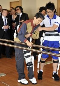 O primeiro-ministro dinamarquês Lars Loekke Rasmussen (atrás, à esquerda) ouve o professor japonês Yoshiyuki Sankai e assiste a sessão de reabilitação com o traje-robô Hal