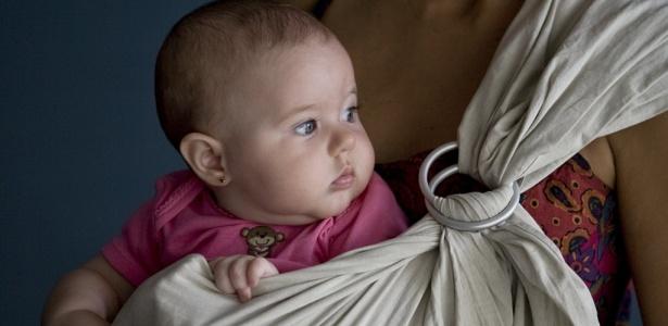 Mulher usa sling para fazer aula de dança com bebê