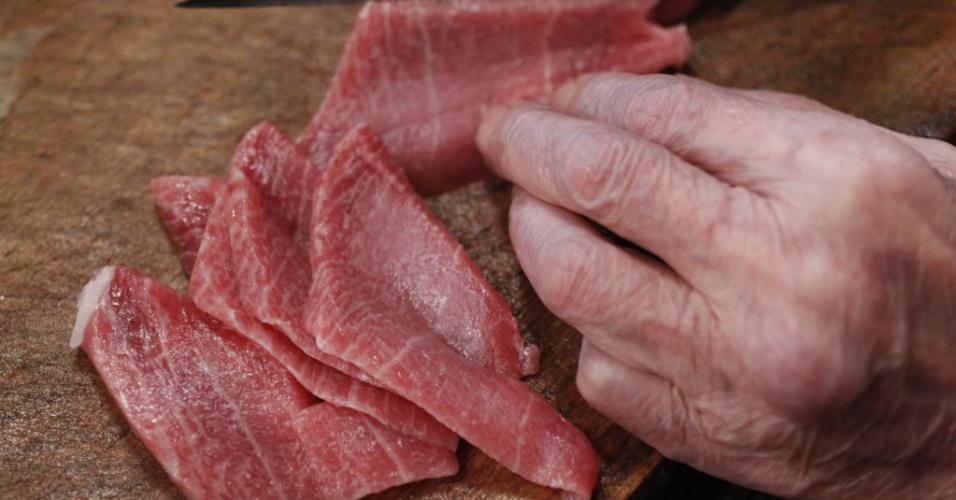 Cozinheiro de sushi corta atum em restaurante em Tóquio