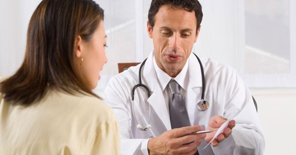 Médico, médico mostrando receita à mulher