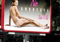 Mulher passa em frente a outdoor com campanha contra a anorexia em Roma